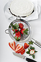 Slices of strawberries, kitchen knife and strainer on white ground, elevated view - CSTF000199