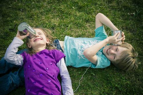 Boy and girl having fun with tin can phone - SARF000408