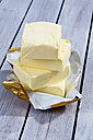 Stack of four pieces of butter on reaseproof paper and wooden table - CSF021130