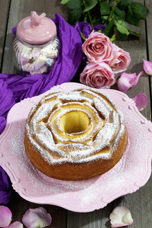 Birthday cake on cake stand, glass of marshmallows and roses in background - CSF021143