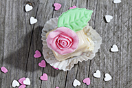 Petit four decorated with rose of marzipan on grey wood - CSF021157