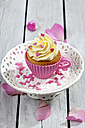 Baking dish formed like cup with decorated cupcake on cake stand and grey wooden table - CSF021147