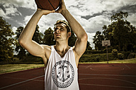 Young basketball player aiming for basketball hoop - GCF000013