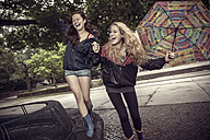 Two playful young women with umbrella in park - GCF000003