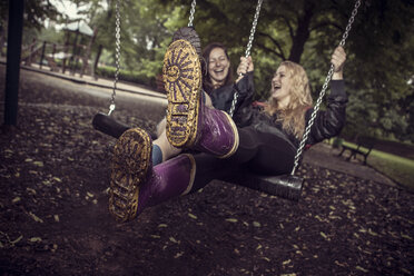 Two playful young women on swing - GCF000002