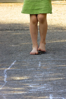 Little girl playing hopscotch with naked feet, partial view - LVF000955