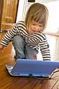 Portrait of little girl using toy computer - LV000948