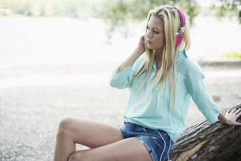 Young woman with headphones sitting on tree trunk - LFOF000152