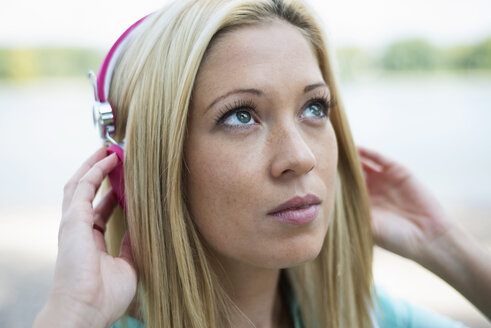 Portrait of young woman with headphones looking up - LFOF000153