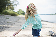 Young woman with headphones dancing on beach - LFOF000155
