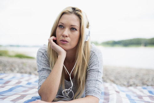 Young woman with headphones lying on a blanket on the beach - LFOF000159