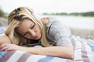 Young woman with headphones lying on a blanket on the beach - LFOF000160