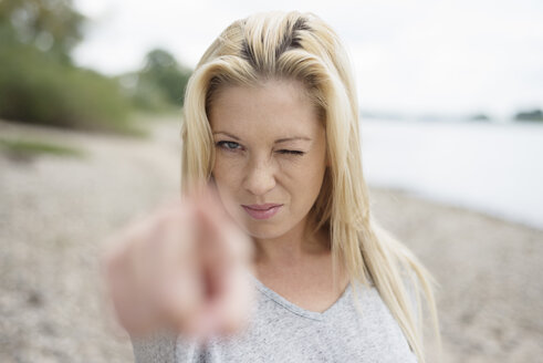 Portrait of young blond woman pointing on viewer - LFOF000164