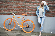 Fashionable young woman leaning at brick wall beside orange bicycle - LFOF000166
