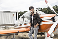 Man with leather jacket leaning on propeller plane - MUMF000020