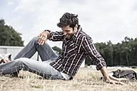 Smiling man sitting on grass - MUMF000046