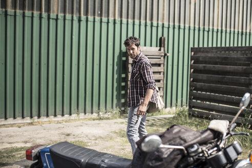 Man standing behind motorcycle - MUMF000035