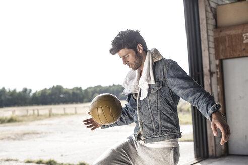 Portrait of man kicking football - MUMF000039