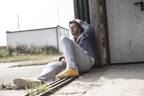 Man sitting on ground watching something - MUMF000043