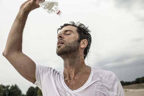 Portrait of man pouring water from bottle over himself - MUMF000027