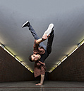Young breakdancer performing a handstand in underpass - STSF000389