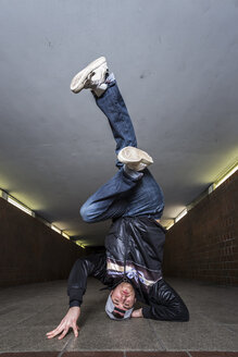 Young breakdancer doing a headstand in underpass - STSF000391
