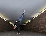 Young breakdancer performing a handstand in underpass - STSF000398