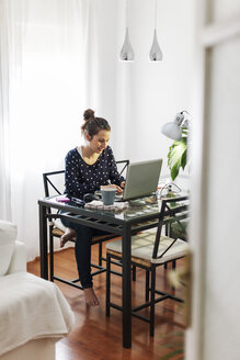 Young woman working with laptop at home - EBSF000122