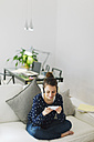 Young woman playing videogames with smartphone at home - EBSF000130