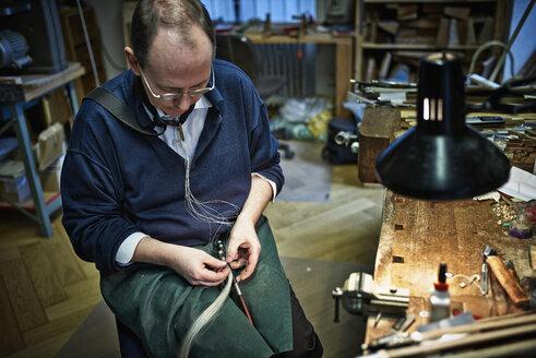 Violin maker repairing a bow - DIKF000084