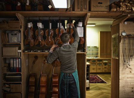 Violin maker in his workshop with restored violins - DIKF000087