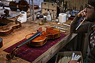 Violin maker at workbench in his workshop - DIKF000095