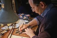 Violin maker in his workshop cutting veneer strips - DIKF000102