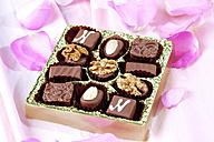Different nougat pralines in chocolate box on pink ground - CSF021169