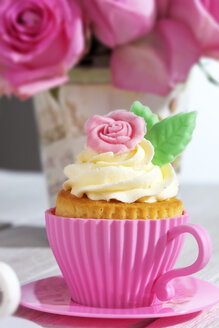 Baking dish formed like cup with decorated cupcakes in front of pink roses - CSF021179