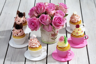 Baking dishes formed like cups with decorated cupcakes and roses on wooden table, elevated view - CSF021182