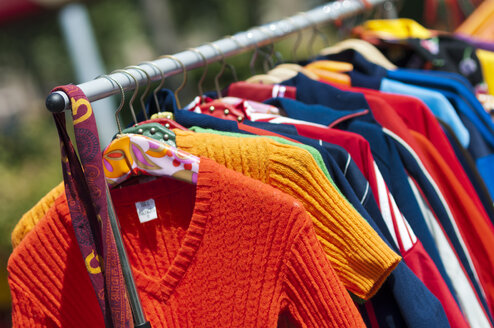 Netherlands, Flevoland, Almere, Colorful second hand clothing on a clothes stand on a market - HAWF000043