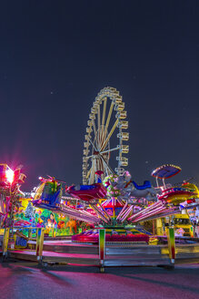 Germany, Hamburg, The ferris wheel and a children's carousel at night - NK000081