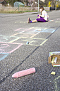 Hopscotch drawing with coloured crayon on asphalt, girl sitting in the background - YFF000081