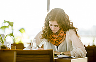 Young woman with note-book writing in cafe - DISF000706