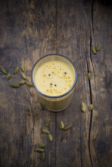Glass of mango lassi and cardamom capsules on wooden table, elevated view - LVF000979