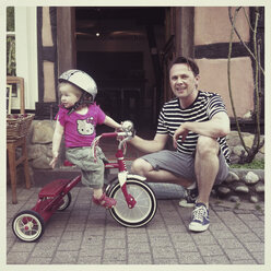 little girl on tricycle in company of her father - IP000101