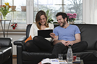 Young couple having fun with tablet computer at home - LAF000718