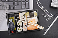 Workplace with sushi on laptop - CSTF000217