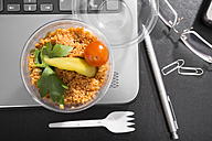 Workplace with vegetable couscous on laptop - CSTF000220