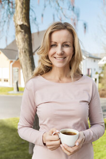 Smiling woman with cup of coffee standing in front of residential area - MFF000967