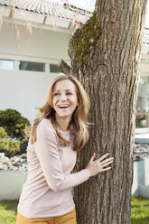 Smiling woman leaning against a tree in front of residential house - MFF000972