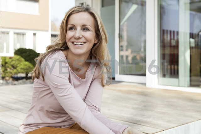 Smiling woman sitting on terrace of residential house - MFF000977