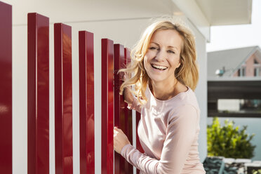 Smiling woman standing by red fence of residential house - MFF000978