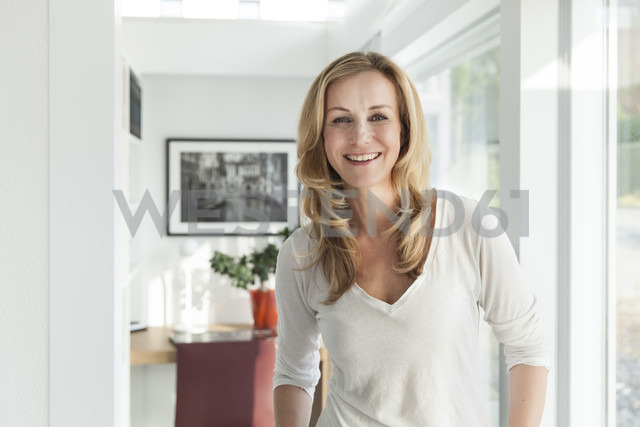Portrait of happy woman standing in her bright modern home - MFF000994
